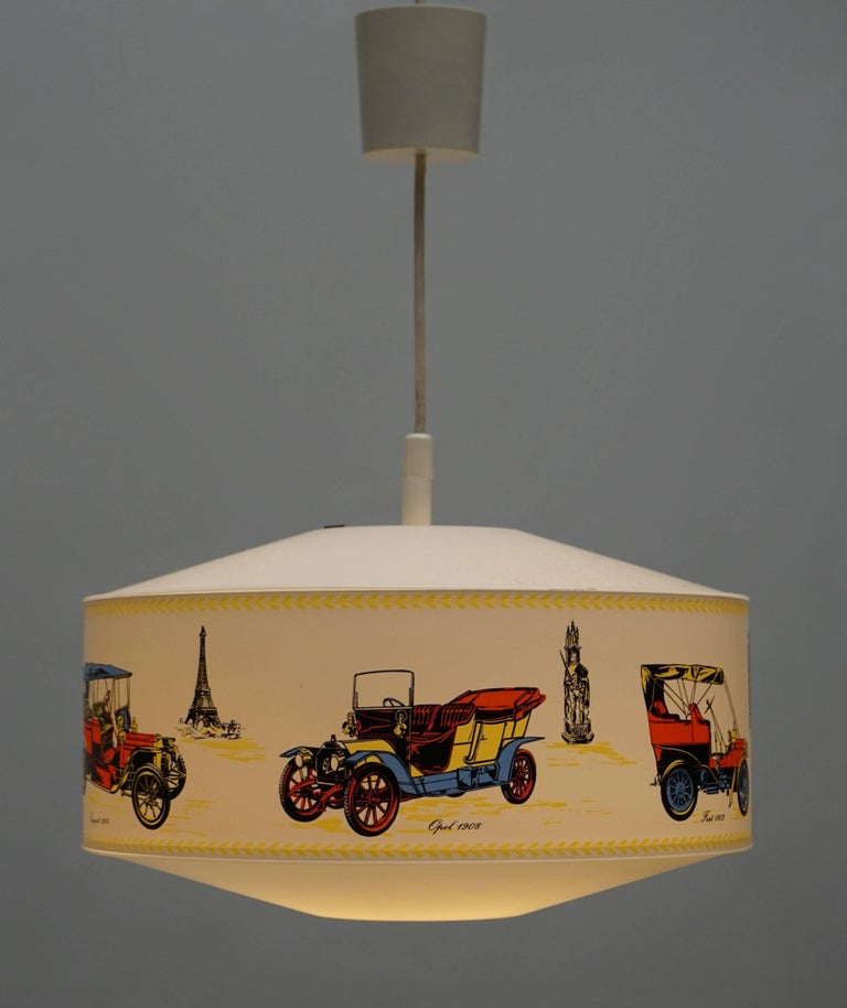 Pendant light decorated with vintage cars, statue of liberty, Eiffel tower, tower of Pisa. Measures: Diameter 35 cm. Height fixture 18 cm. Total height 60 cm.
