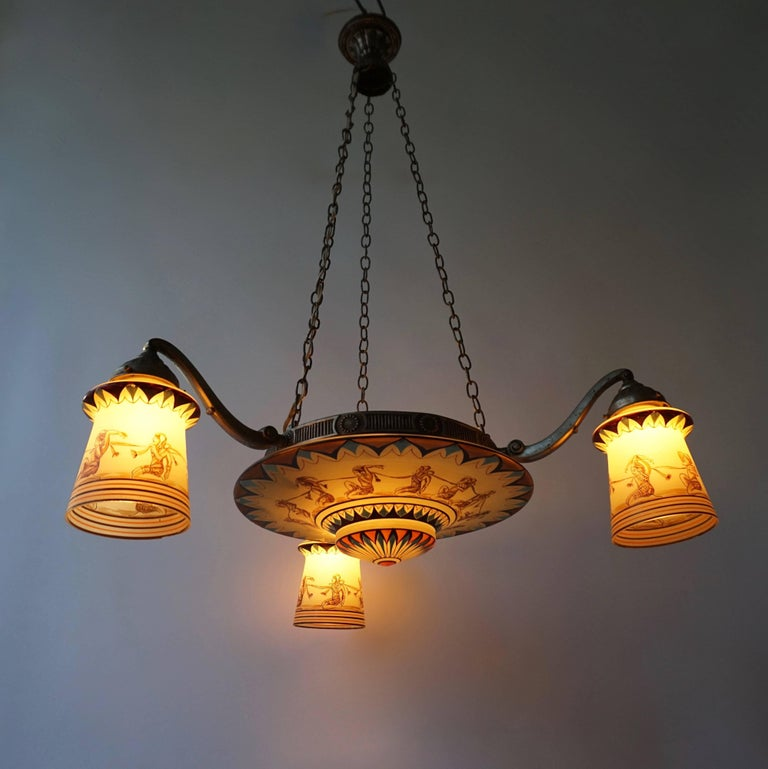 A circular three - branch silvered metal and painted opaline glass chandelier; Art Deco period, circa 1930. The central disc and three lampshades are each decorated in black, red and blue with a row of kneeling figures (argonauts), interconnected