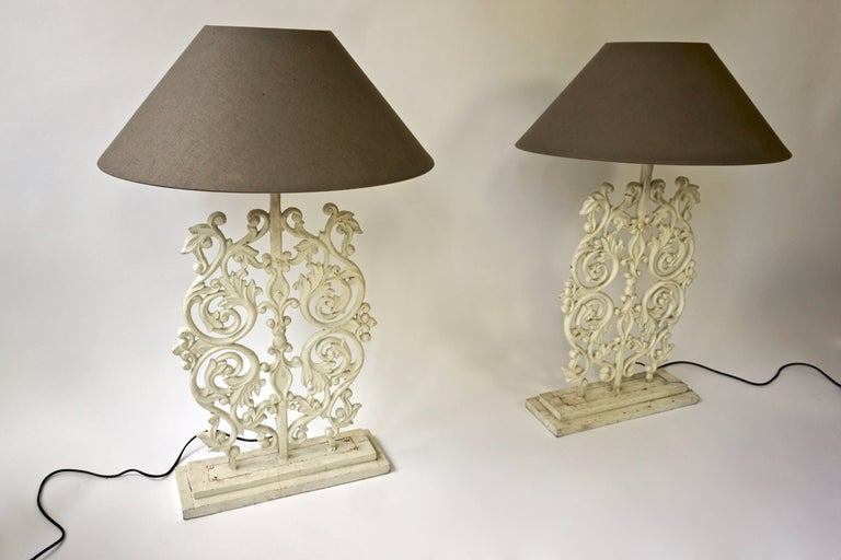 Two white painted iron table or floor lamps.