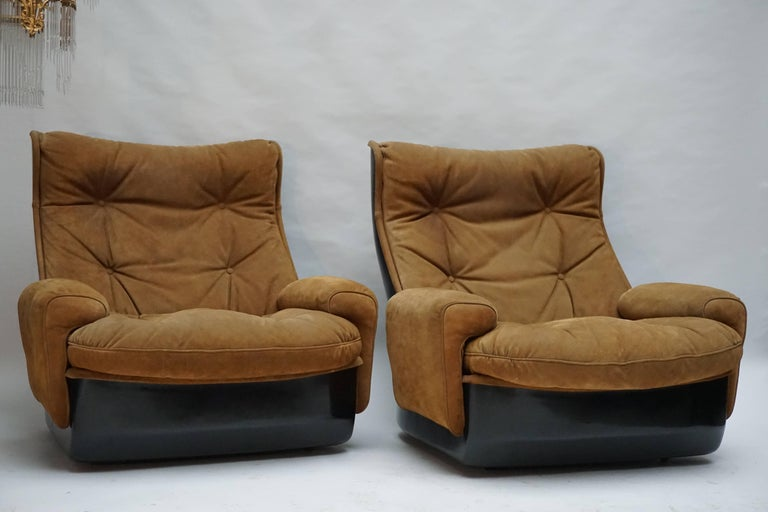 Two lounge armchairs on casters consisting by French manufacturer Airborne International. The shells are made from black fibreglass and the seating is covered in leather buttoned upholstery. This vintage set is in good condition and incredibly