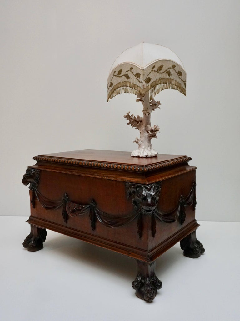 Exceptional small chest or wine cooler in mahogany, partly veneered and on claw-feet, with lion head masks on each corner and garlands at the front on both sides. The cover with lobbed edge. The inside of the cover is covered by zinc. The inside of