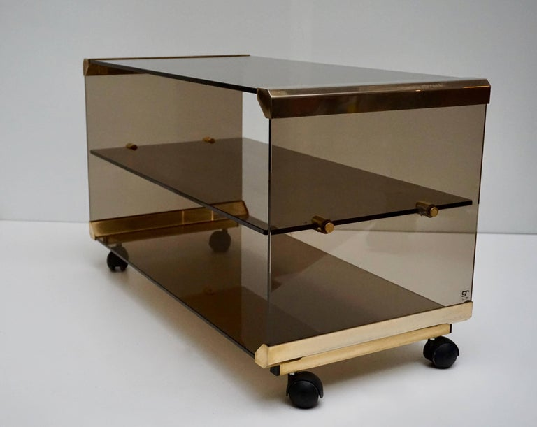 Side tables composed of smoked glass and brass.