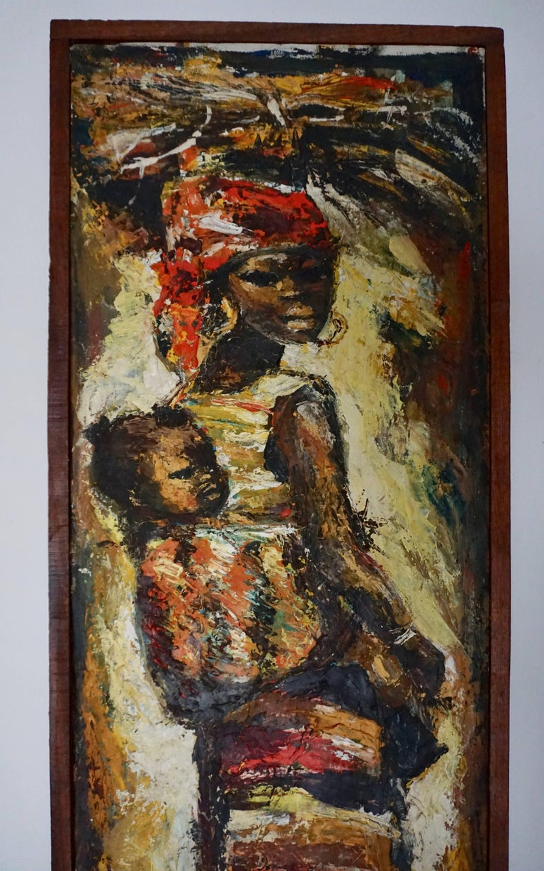 African painting of a woman and her child. It depicts a woman in a colorful dress carrying her child in a sash. The artist signed the piece on the bottom of the painting. Height:84 cm. Width:36 cm. Depth:4 cm.