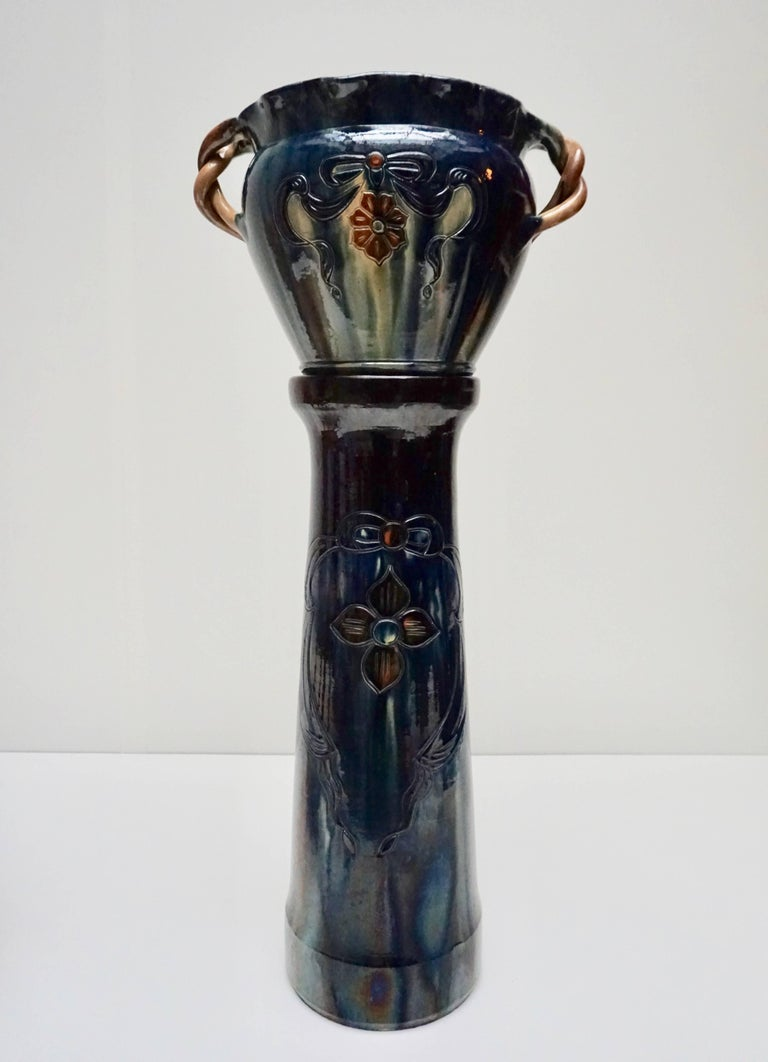 Belgium, an attractive and large one-of-a-kind hand thrown and richly glazed rope handled pot vessel on a stand. Thick and creamily glazed in cream and blue with deep burgundy feather like patterns - special colors that only Belgium artisans