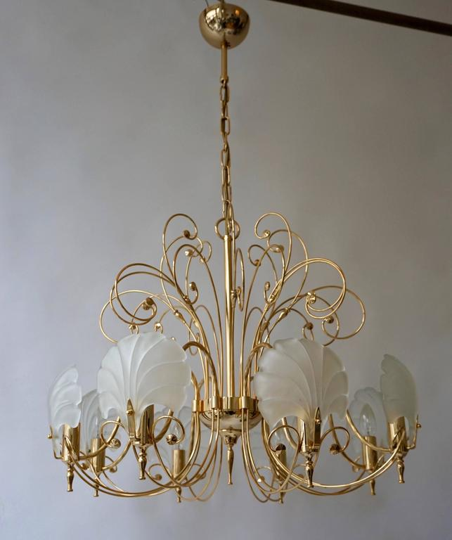 Italian brass chandelier with Murano glass shells.  The light requires eight single E14 screw fit lightbulbs (60Watt max.) LED compatible. Diameter 70 cm. Height fixture 50 cm. Total height with chain 105 cm.