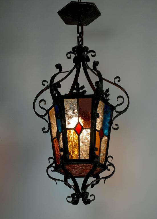 Italian wrought iron and stained glass one light hanging lantern. Originally candle powered. Height lantern: 60 cm. Height with chain: 76 cm. Diameter: 36 cm.