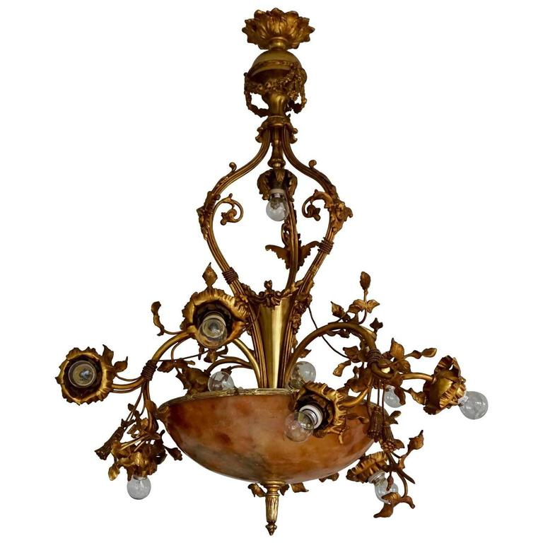 A fine bronze and alabaster Belle Époque chandelier, shaped as swirling and flowering rose branches, early 20th century.  Dimensions: Diameter 75 cm, height 100 cm.