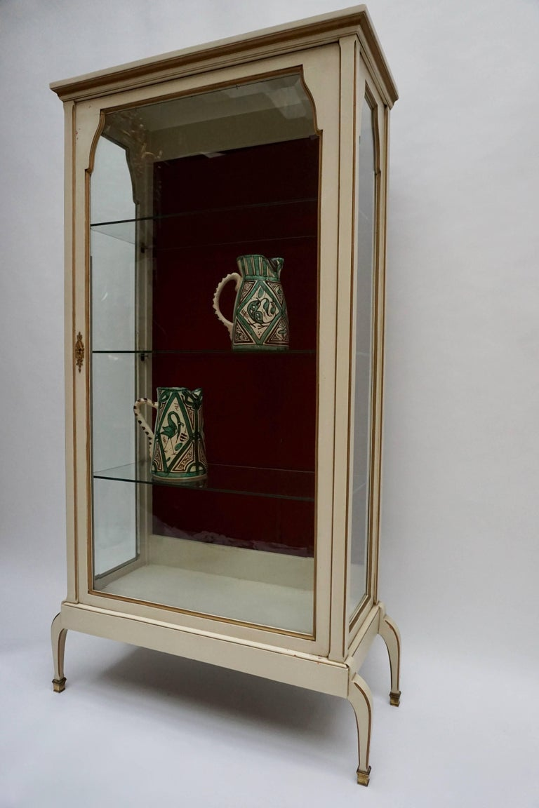 A cream and gold painted wood and glass showcase, resting on curved legs with bronze feet ; 1940ies. The sides with glass panels and one faceted glass front door, all with a serpentine curved top. Inside three glass leaves before a velvet lined back