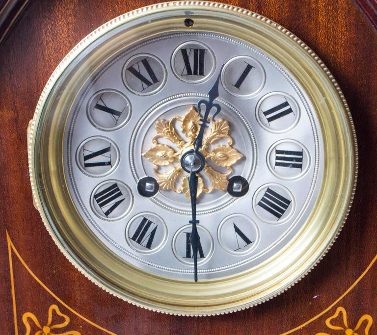 A delighful French marquetry inlaid mahogany lancet-top mantel clock, circa 1900 in date.  With brass and silvered concave dial, Roman chapter ring and gilt rosette centre fronting an eight day spring driven French movement with gong strike..  The