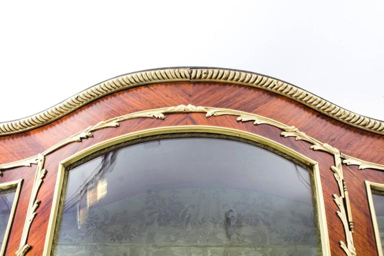 A stunning antique French kingwood Vernis Marten five-panel display cabinet in the Louis XV manner and of extravagantly shaped serpentine form, circa 1880 in date, with exquisite hand-painted decoration and exquisite ormolu mounts.  There are five