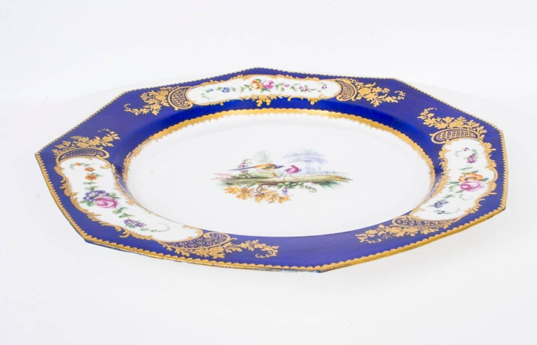 This is a beautiful antique octagonal Sevres porcelain cabinet plate, circa 1880 in date.  The centre hand-painted with fanciful birds, the rim with three oval cartouches, each with summer flowers on a beautiful cobalt blue ground with gilt dental