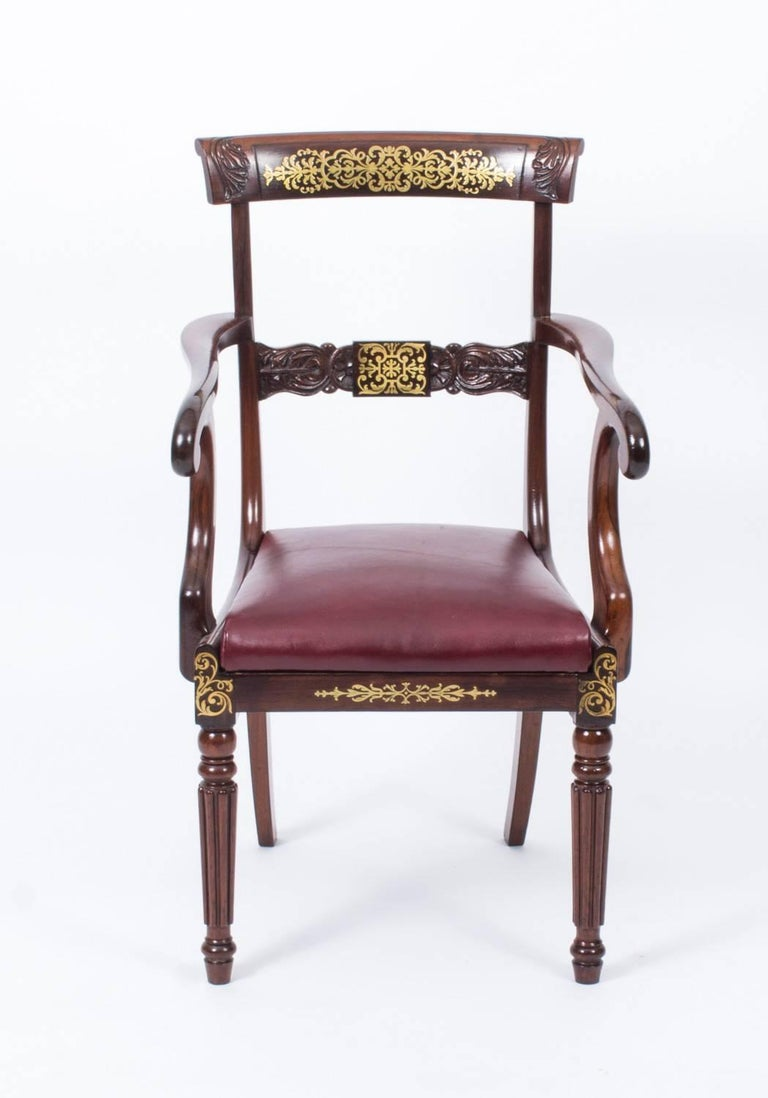 This is an elegant antique Regency mahogany and cut brass marquetry elbow chair, circa 1815 in date.  It has a beautiful curved cresting rail and a central bar profusely inlaid and carved with acanthus, and the pair of downswept arms have elegant
