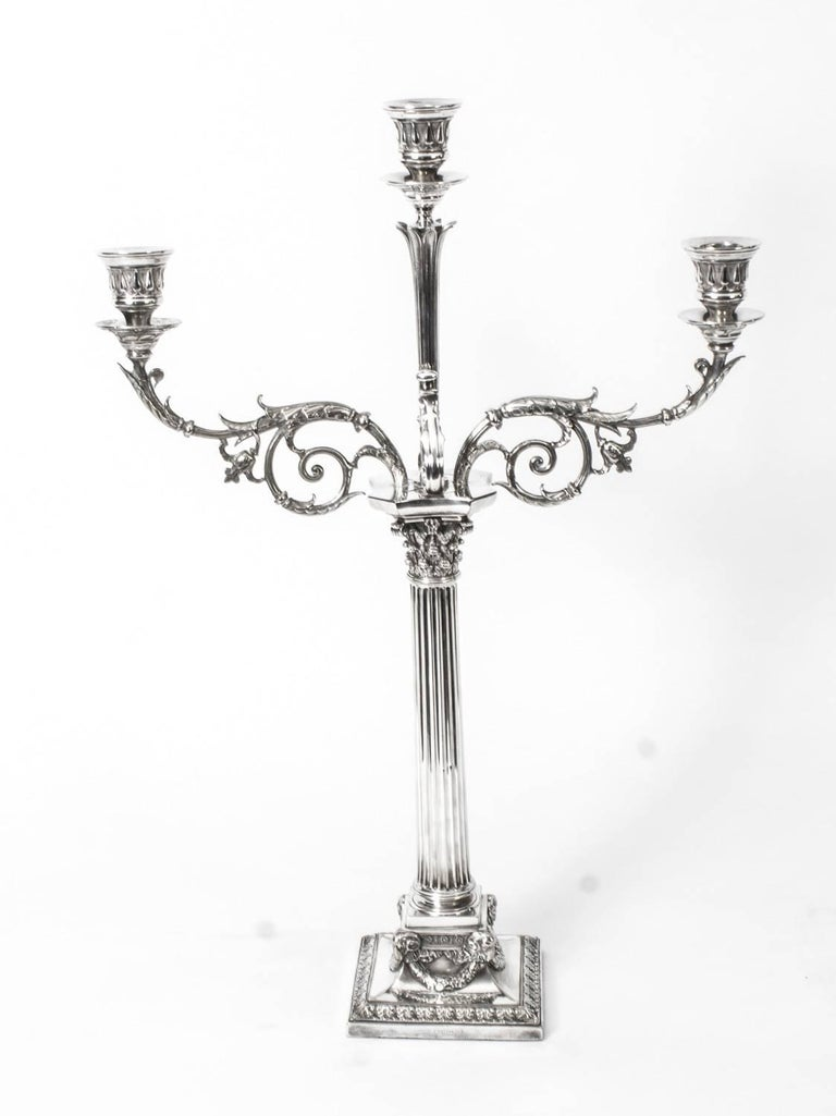 This is a stunning pair of antique Victorian silver plated, three light, two-branch table candelabra, circa 1865 in date, and each bearing the makers mark of the renowned English silversmiths Elkington & Co.  The candelabra each feature a Corinthian