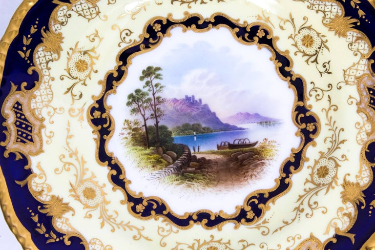 This is a beautiful antique shaped circular Coalport Named View porcelain cabinet plate signed E. Ball and dated 1891.  The central hand-painted scene of Lake Menteith is set within a yellow and cobalt blue border heightened with raised gilt and