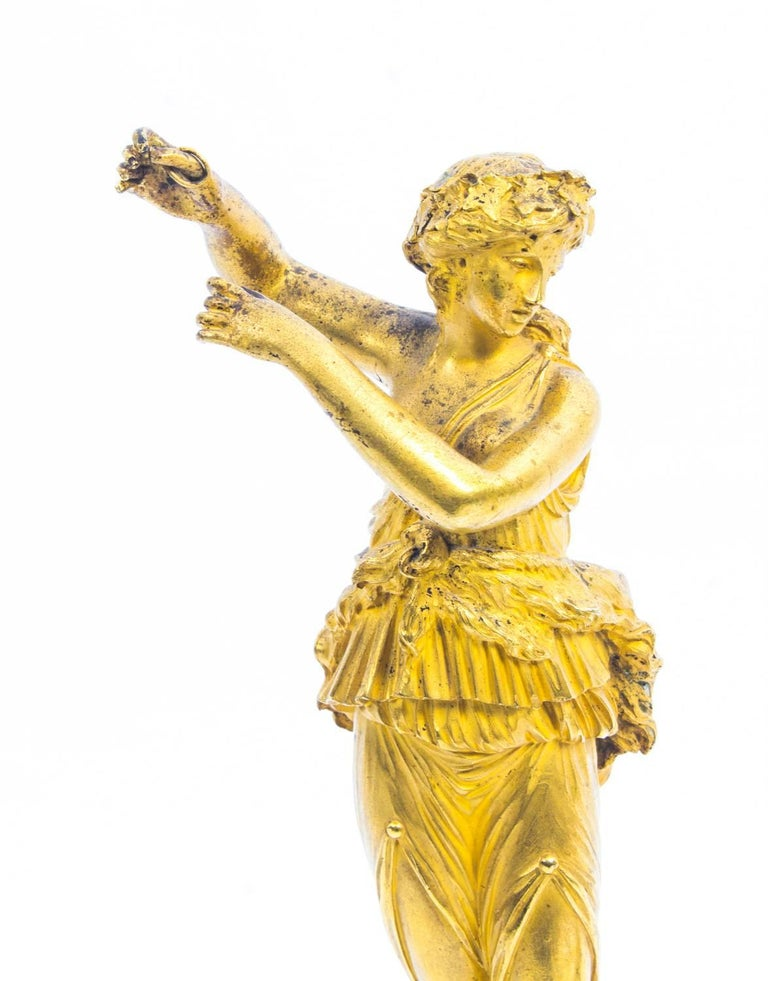 This is a delightful antique pair of French ormolu classical dancing maidens, circa 1820 in date.  They are raised on cylindrical socles with square plinth bases. The wonderfully chased and detailed maidens are each dressed in flowing classical