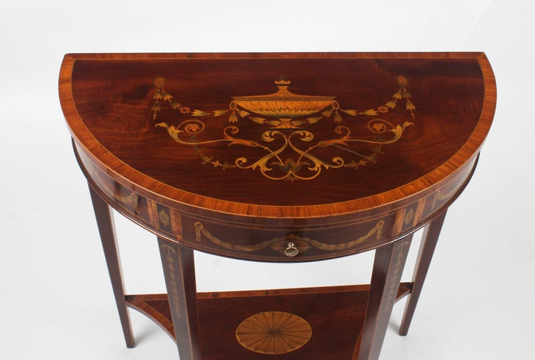 This is a beautiful antique English Regency Revival mahogany and marquetry demilune console table, circa 1900 in-date.  The half-round table top is beautifully framed with a satinwood border and has a finely inlaid marquetry central urn within