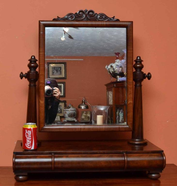 This is an antique English dressing table swivel mirror, circa 1840 in date.   It is made from flame mahogany and has a useful drawer underneath for storing your brushes and combs. The mirror has hand carved floral decorations to the pediment.