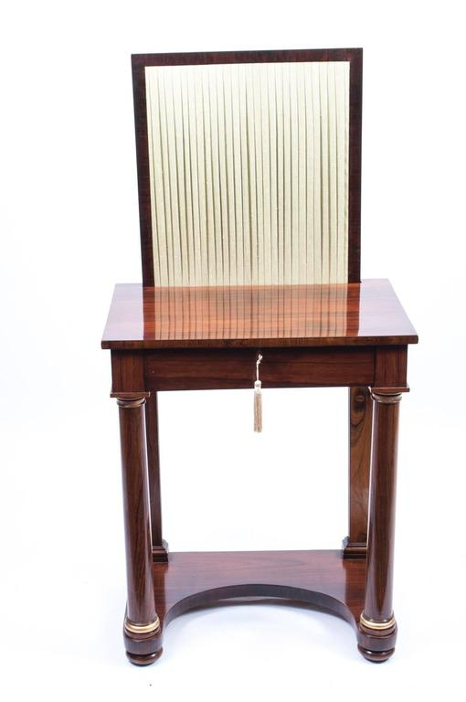 This is a beautiful small antique English Empire rosewood console or writing table with integral writing slide and pen drawer circa 1820 in date.  This dual purpose table has a drawer above a pair of elegant tapering columns with gilded mounts to