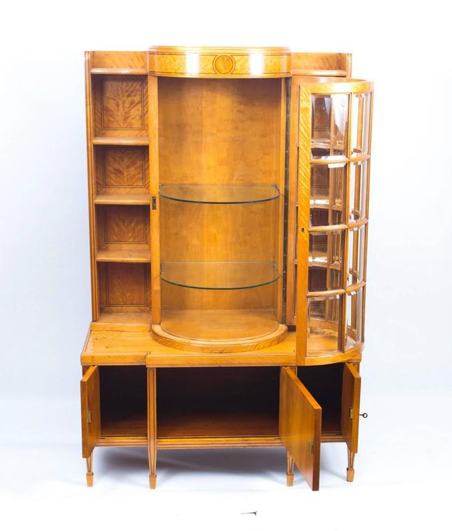 This is a superb antique late 19th century satinwood display cabinet, outlined throughout with boxwood and ebony stringing. It has a decorative central bowed door with twenty bevelled glass panels, opening to reveal two adjustable glass shelves. The
