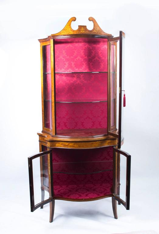 This is a stunning English Edwardian serpentine mahogany display cabinet, circa 1900 in date with exquisite hand cut inlaid decoration.