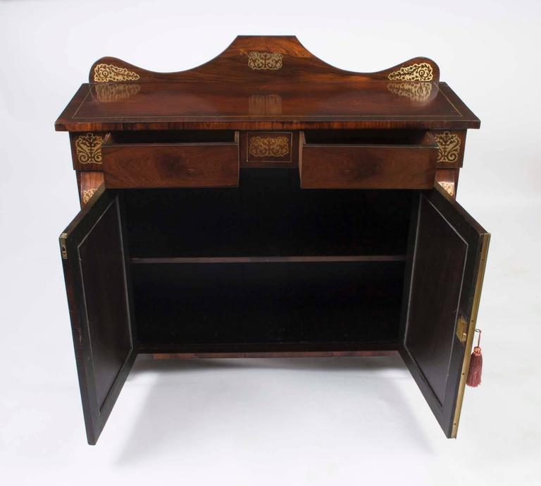 This is an elegant antique Regency period brass inlaid rosewood chiffonier circa 1820 in date.