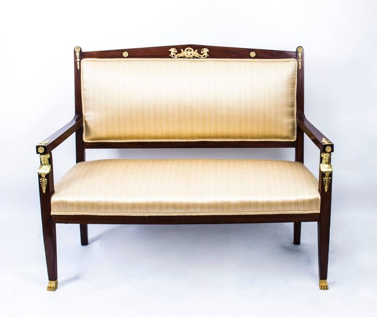 This is a fantastic and highly decorative antique French Empire three-piece salon suite, comprising a sofa and a pair of armchairs, circa 1880 in date.  It has been crafted from fabulous solid mahogany and is smothered in fabulous high quality