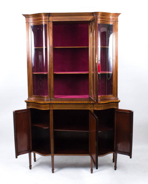 A stunning antique English Edwardian mahogany serpentine display cabinet, circa 1900 in date, of the very highest quality, with inlaid decoration, typical of Edwards and Roberts furniture.