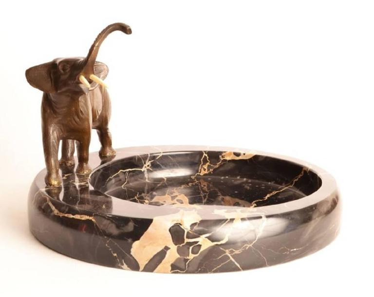 This is an antique bronze sculpture of a distinguished old elephant with fabulous tusks set on an attractive marble base, circa 1920.
