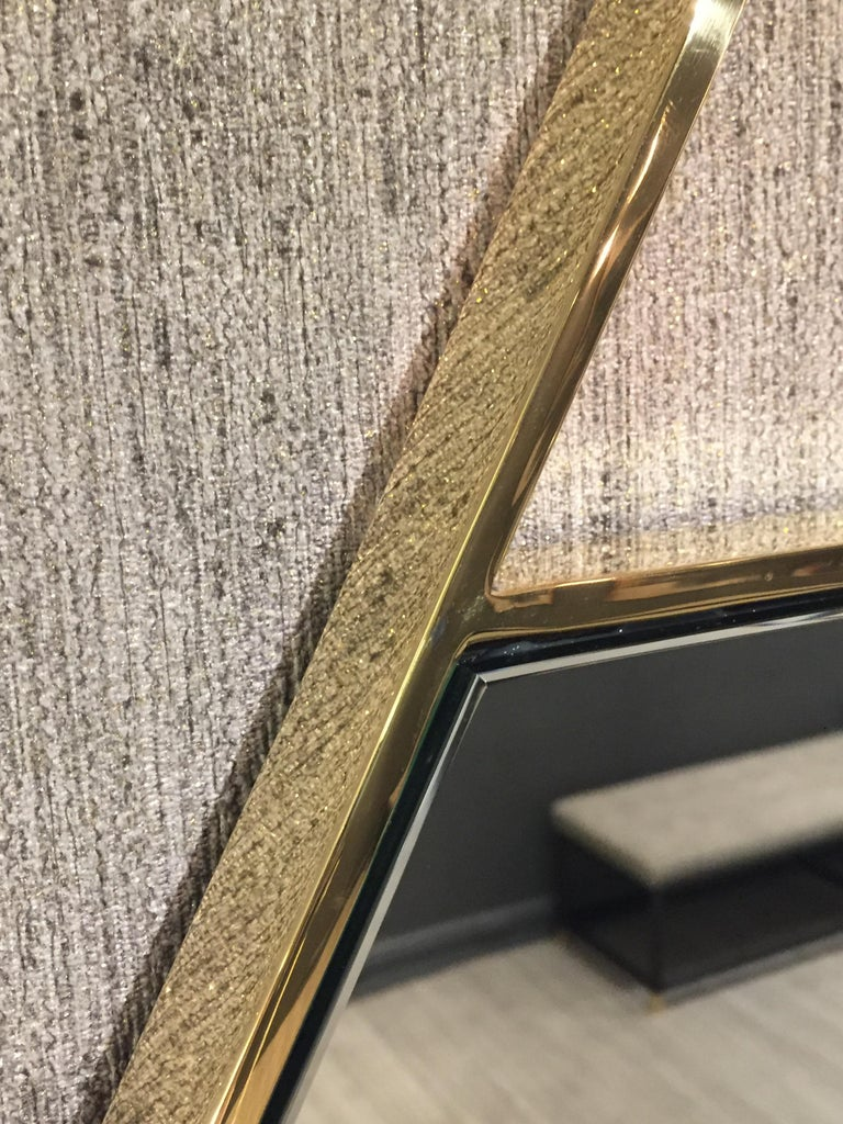 The Cosmopolitan mirror, designed by Irwin Feld for CF Modern, is a 5 sided mirror with a brass frame. The upper triangle is left open as a decorative false hanger. Shown here in polished brass.