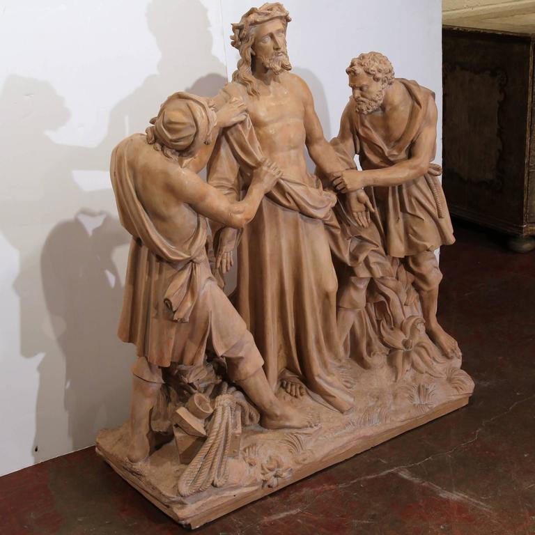 This large, antique sculpture was crafted in France, circa 1860; it depicts the tenth station of the cross when Jesus clothing are being removed. In the biblical composition, Christ is being stripped of his garments by two soldiers. The monumental,