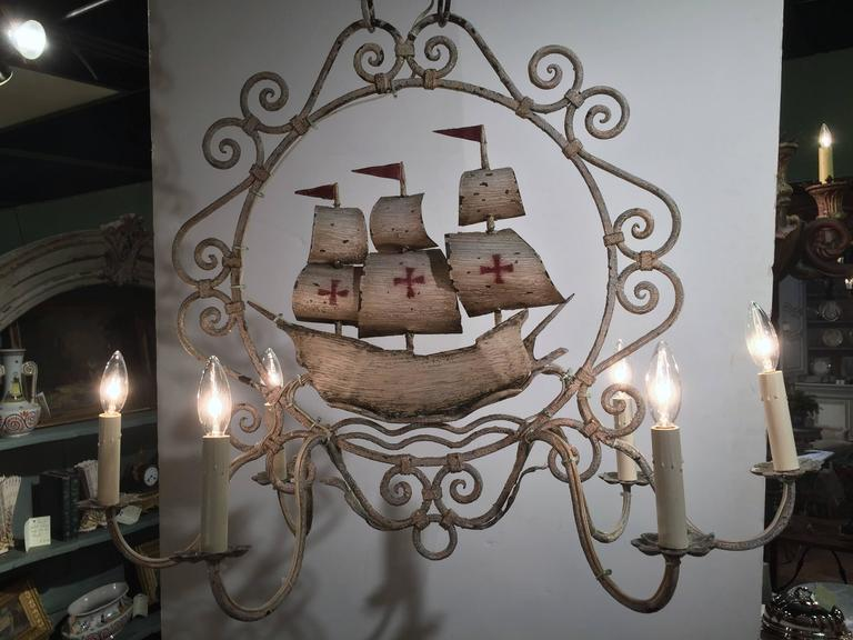 This interesting vintage chandelier was crafted in Normandy, France, circa 1960. Oblong in shape, the fixture has six newly wired lights and is hand painted in a beige, off-white palette. In the middle of the frame is a Classic ship with sails and