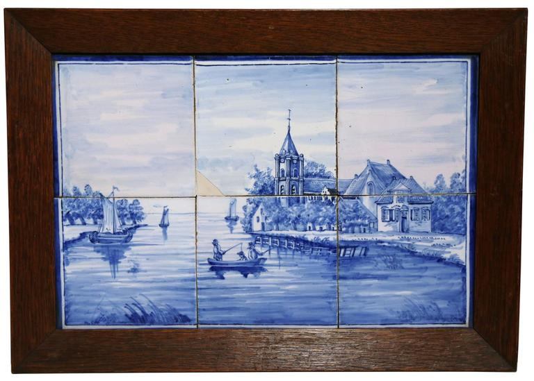 This elegant pair of antique ceramic Delft tiles were created in France, circa 1860. Each of the six porcelain faience tiles are set into wooden frames and feature hand-painted illustrations typical of the traditional Delft style. The Dutch motifs