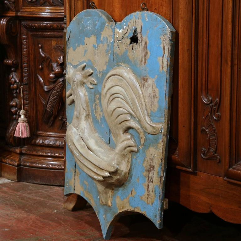This antique wooden signboard was crafted in France, circa 1780. Interesting in shape and in excellent condition, the board features a French rooster in tole relief. Both the board and bird have the original blue paint finish and the original chain