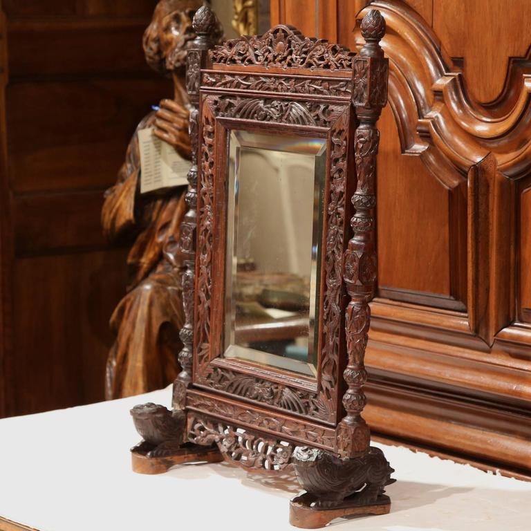Decorate a counter with this elegant antique makeup mirror frame from the Alps of France. Crafted, circa 1860, the rectangular, tilt-top mirror with beveled glass sits on two pedestal legs and features Fine, intricate floral and foliage carvings