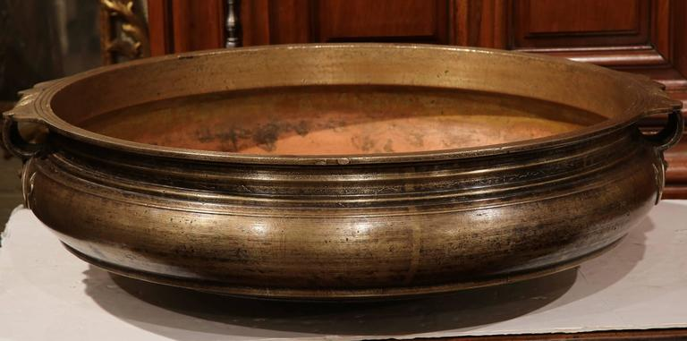 Decorate a table or countertop with this elegant bronze cooking dish. Crafted in Southern India, circa 1860, the antique Urli has a neoclassical shape with wide mouth, short height and handles on both sides and Fleurs-de-Lys detail. This dish was a