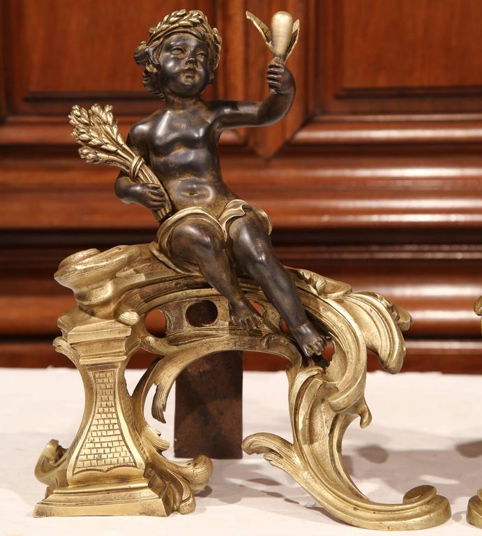 Decorate your fireplace with this elegant pair of antique bronze chenets. Crafted in France, circa 1860, the sculpted andirons feature patinated cherubs holding flowers and sitting on a base reminiscent of the Rococo style. The set is in excellent