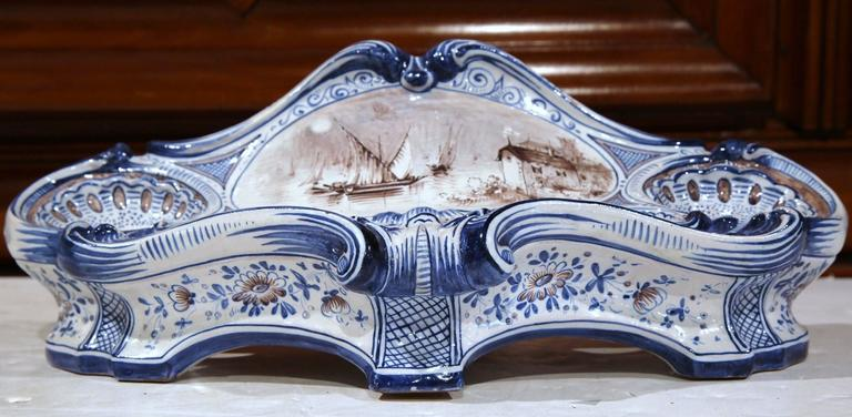 This uniquely shaped ceramic inkwell was sculpted in France, circa 1880. The cartouche-shaped desk essential features a hand-painted black and white center medallion with sailboats, a house and flowers. The blue and white palette along with the