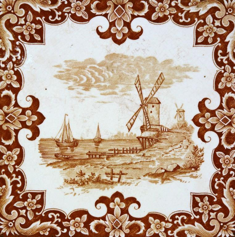 This interesting, antique hot dish tray was crafted in France, circa 1870. The piece features a hand-painted centre tile with a windmill and sailboats in a brown and white palette. The ceramic tile is set inside a carved wood frame. The tray