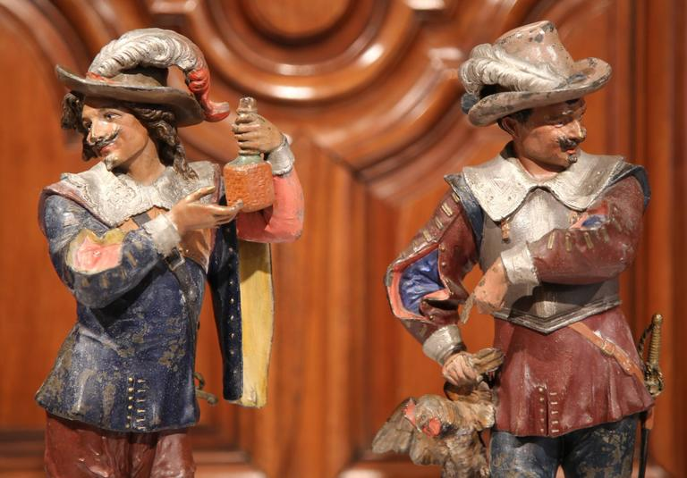 Decorate a mantel or a shelf with these elegant and colorful antique statues. Crafted in Southern France, circa 1870, each metal sculpture features a realistic, expressive musketeer in traditional outfits; one man is pointing at the rooster he just