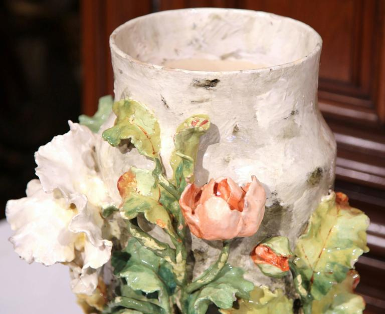 This beautiful, hand-painted majolica vase was sculpted in Montigny sur Loing, France, circa 1870. This colorful pot is embellished with large flowers in high relief in a pink, orange and white palette. The vase has a large mouth, and would make an