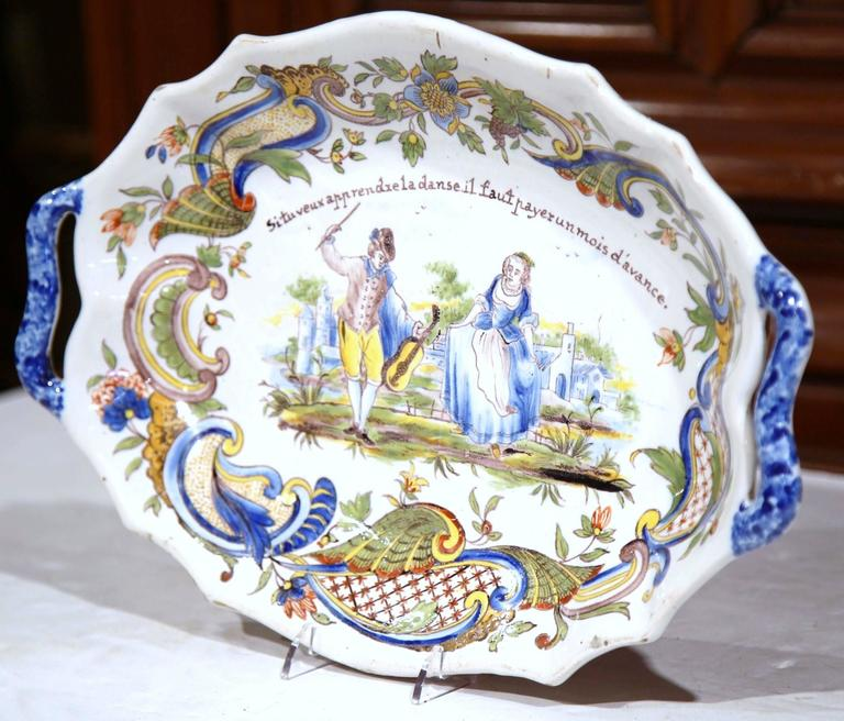 This beautiful antique ceramic dish was crafted in Normandy, France, circa 1880. The stylized ceramic plate has a scalloped edge and depicts a hand painted courting scene with a violinist teaching a young woman how to dance. The French motto reads: