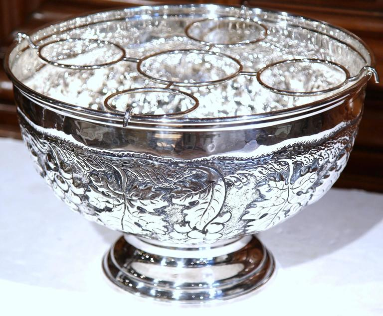 Keep your wine or champagne chilled in style with this elegant round bucket from France. The outside features intricate repousse decorative motifs of grapes and vines. Inside the bucket, two removable trays will hold up to five bottles. This silver