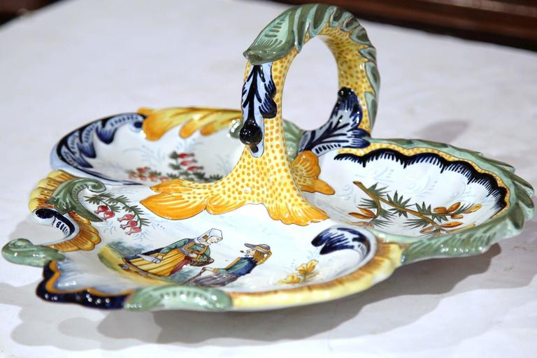 This colorful, antique Quimper dish with handle was sculpted in Brittany, France, circa 1950. This triangle shaped porcelain tray features three unique food compartments decorated with hand-painted flowers and a Briton couple dressed in traditional