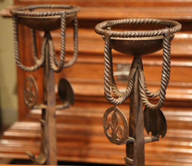 These antique wrought iron andirons were forged in France, circa 1820. This kind of andirons which feature a cupped, round shaped top, are called a