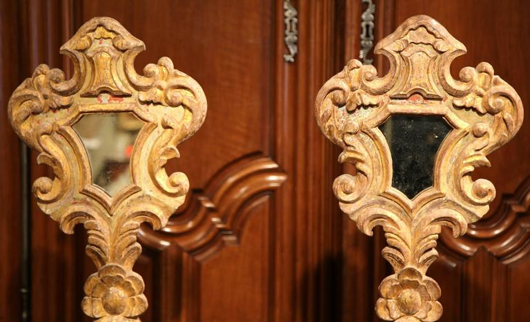 Embellish your mantel with this elegant pair of antique mirrors from Italy. Crafted, circa 1820, each tall hand carved church reliquary sits on a rectangular base, and features hand carved scroll decor including a shell motif at the bottom. Both