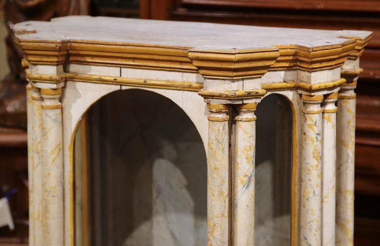 This beautifully painted antique reliquary was crafted in Italy, circa 1760. The theatrical Baroque cabinet features ten columns separated by five glass doors arranged around the religious vitrine. The unique, stylish reliquary has its original