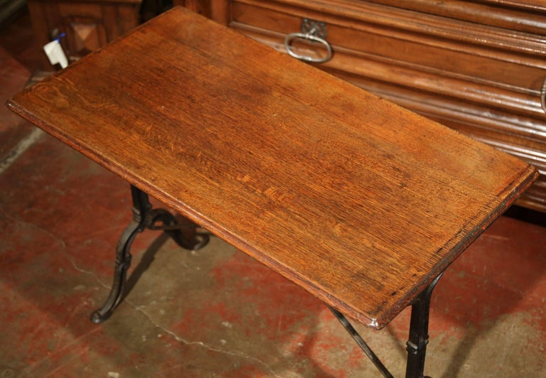 This antique bistrot table would make the perfect addition to a small room or breakfast nook. Crafted in Paris, France, circa 1900, and used in bistrots, the table has an intricate cast iron base and stretcher, which is topped with a sturdy wooden