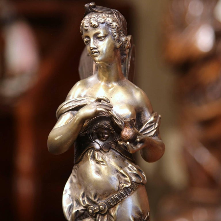 This elegant detailed bronze statue was created in France, circa 1860. The female figure features a Classical Roman woman with wings standing on a dolphin and holding a small jar in her left hand. The bronze statue is mounted on a sturdy round base