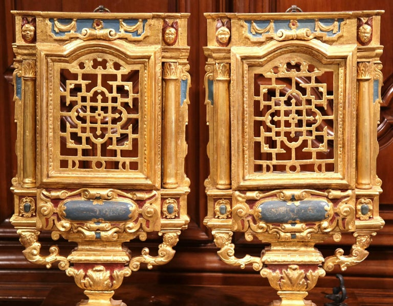 This beautiful pair of antique decorative carvings were hand-carved in Italy, circa 1780. Each of the ornate wall hanging sculptures features a polychrome and gilt vase supported by two columns on each side and a stationary door in the center. The