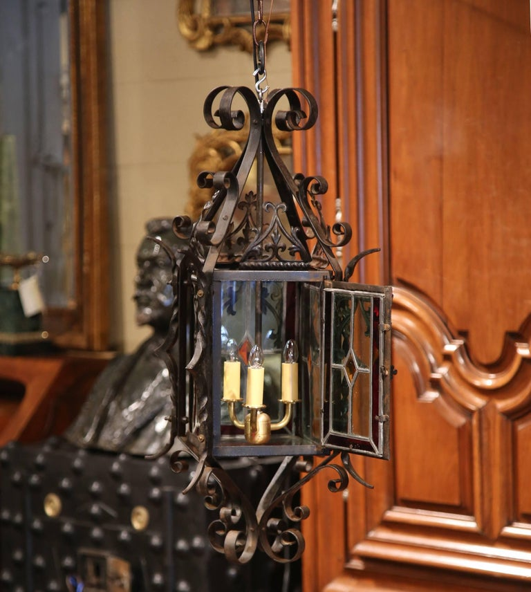 For a unique lighting feature, look no further than this beautiful, antique lantern from France. Crafted, circa 1870, the three-light chandelier features four painted, stained glass panels embellished with fleurs-de-lys, and a small door to access